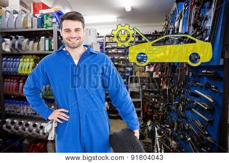 Smiling male mechanic holding tire against full store room