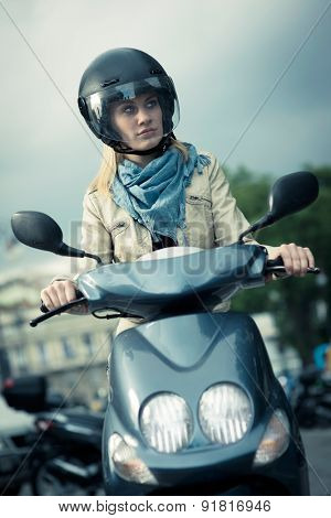Girl riding motor scooter