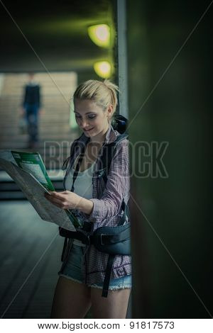Young female backpacker using map in a subway