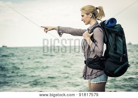 Young female backpacker by the sea, pointing at something