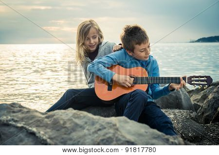 Cute children with guitar by the sea
