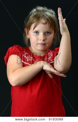 Small girl making some exercise with her arms on black
