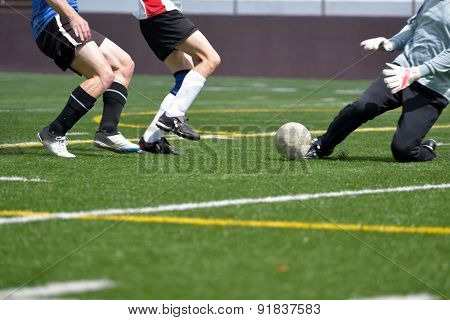 Adult, male, soccer striker, sweeper and goalkeeper going for the ball