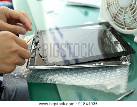 People hands repair the damaged ipad