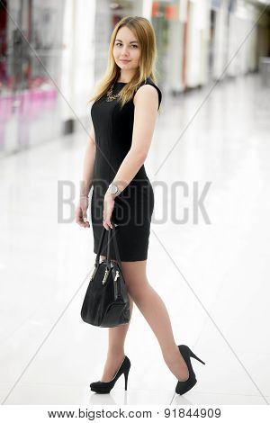 Young Woman In Black Dress In Shopping Mall