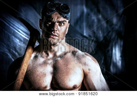 Muscular dirty coal miner with a pickaxe over dark grunge background. Mining industry. Art concept.