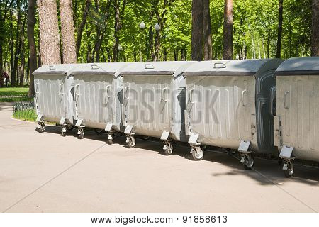 Several Containers Of Trash On An Asphalt Site