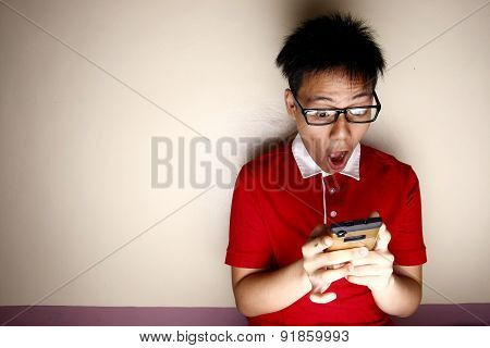 Teenage kid using a smartphone and acting surprised
