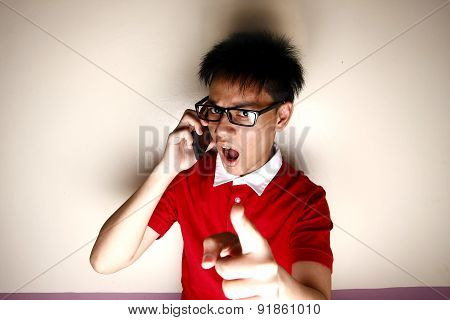Angry Teenage kid talking on a smartphone and pointing at camera