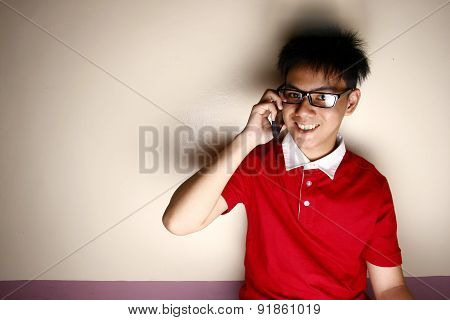 Teenage kid talking on a smartphone and smiling