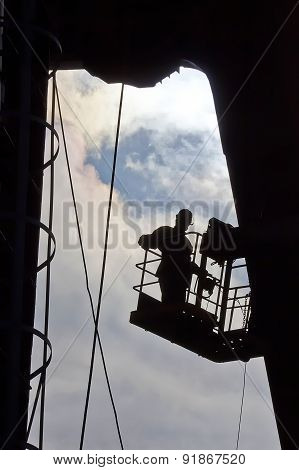Silhouette Of Builder Working At Height. Industry
