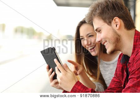 Couple Sharing Media Content From A Tablet