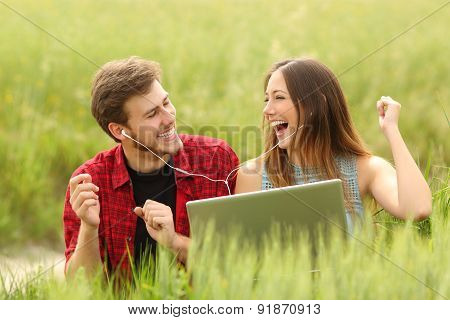 Couple Singing And Listening Music From A Laptop