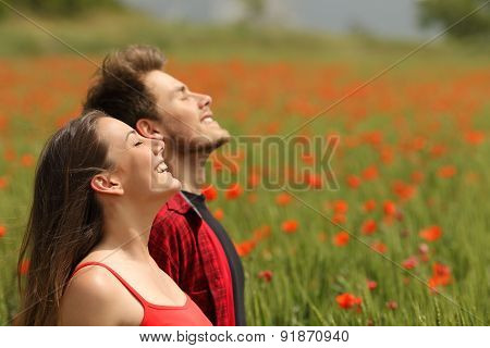 Happy Couple Breathing Fresh Air In A Red Field