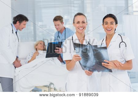 Smiling doctors discussing about patients file in hospital room