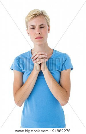 Pretty blond woman praying on white background