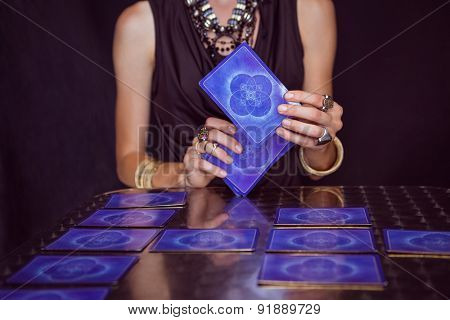 Fortune teller forecasting the future with tarot cards on black background