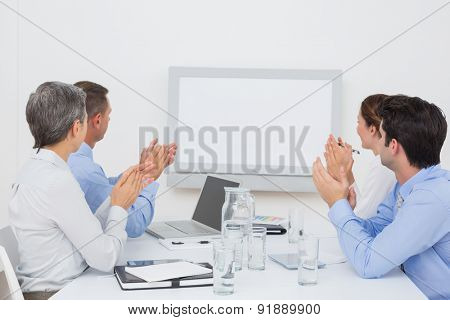 Business team applauding and looking at white screen in the meeting room