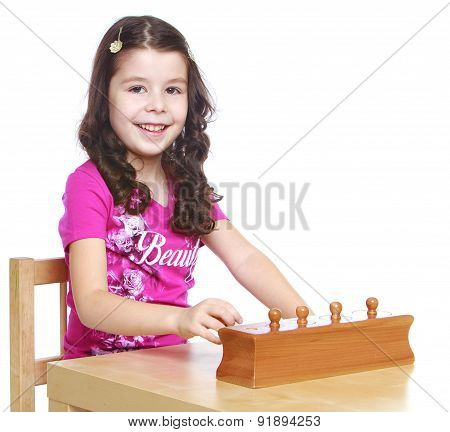 Smart girl  sitting at the table  learning Montessori material