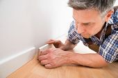 Close-up Of A Carpenter Leaning On Floor Applying Skirting On Wall poster