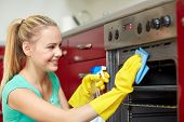 people, housework and housekeeping concept - happy woman with bottle of spray cleanser cleaning oven at home kitchen poster