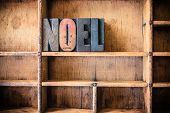 The word NOEL written in vintage wooden letterpress type in a wooden type drawer. poster