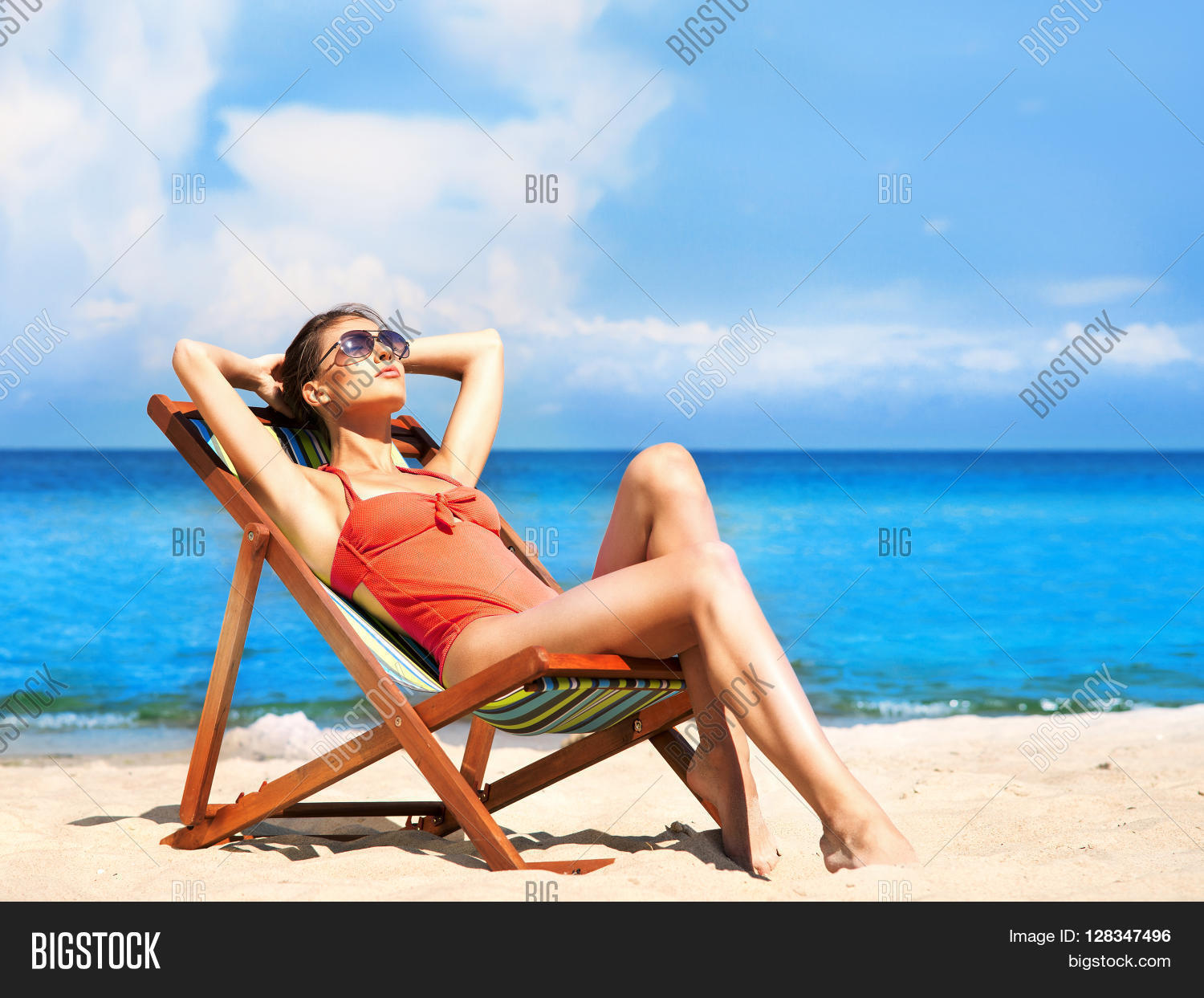 Beautiful, Seductive Girl In Alluring Swimsuit Getting A Suntan While Lying  In The Sun Chair