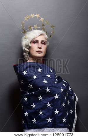 Portrait of mature fashion or vogue woman posing for American magazine over gey background in studio. USA flag concept.