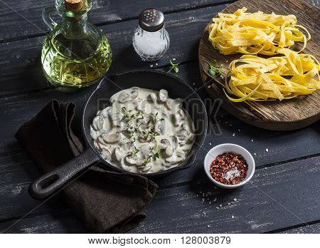 Ingredients for cooking pasta with creamy mushroom sauce - dry pasta mushroom cream sauce olive oil and spices. On a dark wooden background. Healthy delicious food