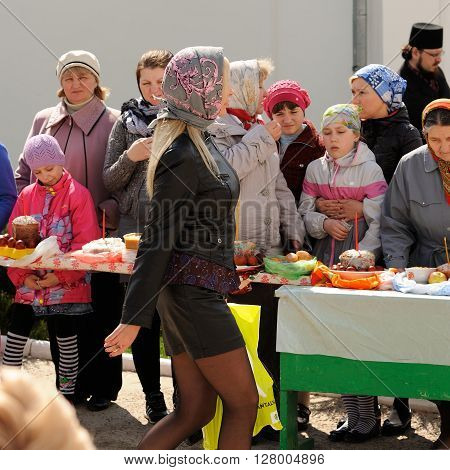 Orel Russia - April 30 2016: Paschal blessing of Easter baskets in Orthodox church. Girl in short skirt passing by women with kulichi closeup