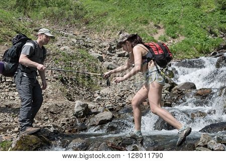 KAMCHATKA PENINSULA RUSSIA - JUNE 23 2012: Summer hiking - tourist man helps a girl-tourist to crossing the mountain river in a summer sunny day on Kamchatka Peninsula. Eurasia Russian Far East Kamchatka Region.