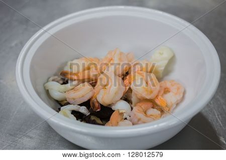 Fresh grilled shrimps with lemon on a pot of soup.