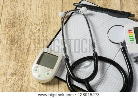 stethoskope on wooden desk with blood pressure measurement copy space