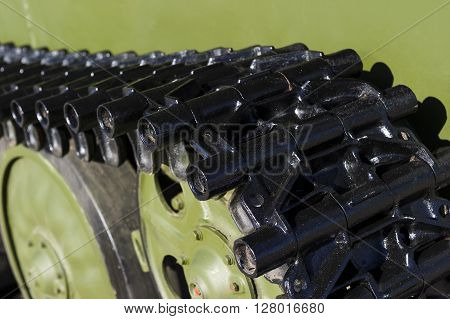 Tank tracks and steel wheels of heavy armored vehicle with green bodywork, military industry, modern army equipment, selective focus