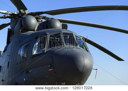 Military heavy helicopter, army air means of transport, air force, aviation and aerospace industry, grey big copter with rotor in sunny evening, blue sky on background
