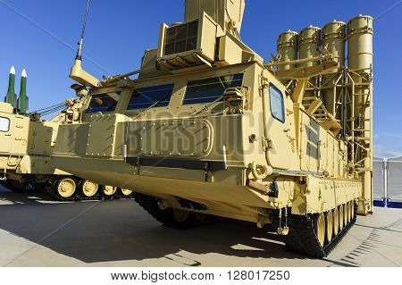 Antiaircraft missile complex, ballistic launcher with big four missiles ready to attack on military powerful all-terrain transportation with blue sky on background, modern army industry