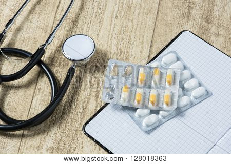 stethoskope on wooden desk with pills pencil and notebook copy space