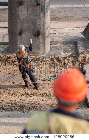 Tyumen, Russia - July 31, 2013: JSC Mostostroy-11. Bridge construction for outcome of the Tobolsk path and Bypass road round Tyumen. Worker pulls rope to level panel lifted by crane