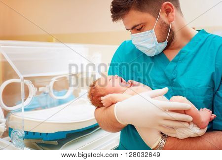 Young Adult Man Holding A Newborn Baby In Hospital