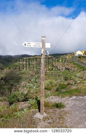 Fingerpost on a trail up from the Valle Gran Rey to the mountain village El Cercado. The town is well known as pottery town on La Gomera. The finger shows the path to go. In the background, trade wind with big clouds in the highlands