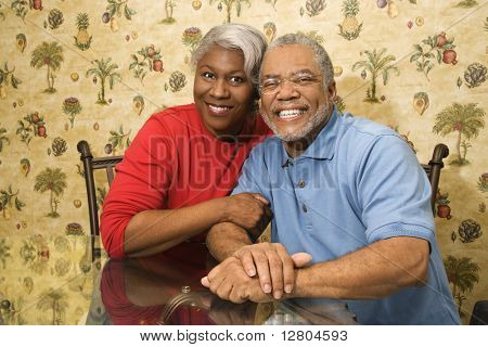 Portrait of mature African American couple embracing and smiling at viewer.