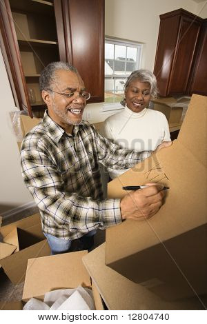 Middle-aged African-American male labeling moving box with wife in background.