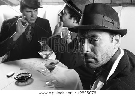 Three Caucasian prime adult males in retro suits sitting at table.