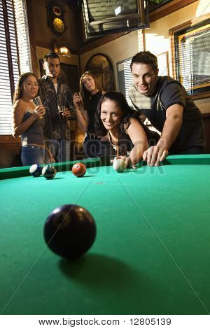 Young caucasian woman receiving advice on shooting pool ball while playing billiards.