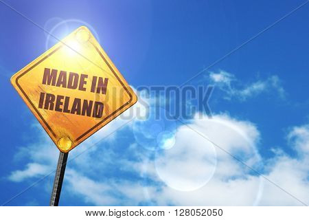 Yellow road sign with a blue sky and white clouds: Made in ireland