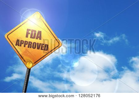 Yellow road sign with a blue sky and white clouds: FDA approved