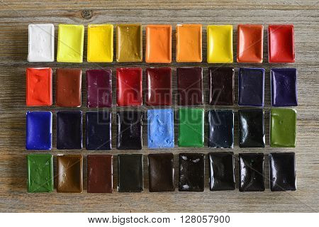 a lot of watercolors on wooden background