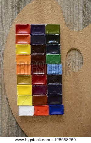 watercolor paint and palette on wooden background