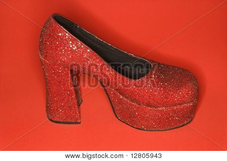 Red glitter high heel shoe against red background.