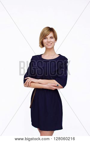 Attractive young woman in a blue dress with crossed hands smiling and looking at camera.